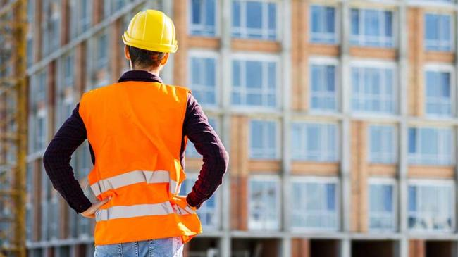 A construction worker standing in front of a building