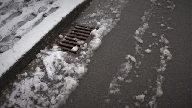 A street drain, pavement and melting snow all around
