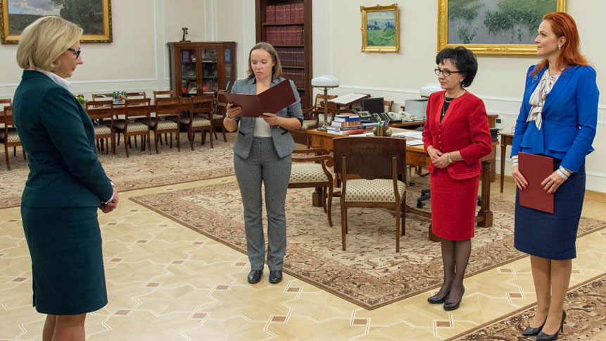 Małgorzata Motylow listing to the official presentation of the nomination act by the Sejm representative, next to the Speaker of the Sejm, Elżbieta Witek and head of the Chancellery of the Sejm Agnieszka Kaczmarska