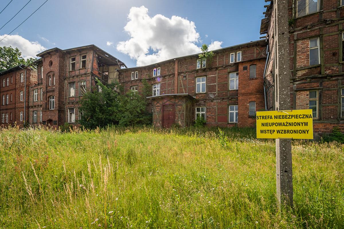 Fotografia przedstawia zrujnowany budynek po KL Soldau wDziałdowie ztablicą zakazującą wejścia