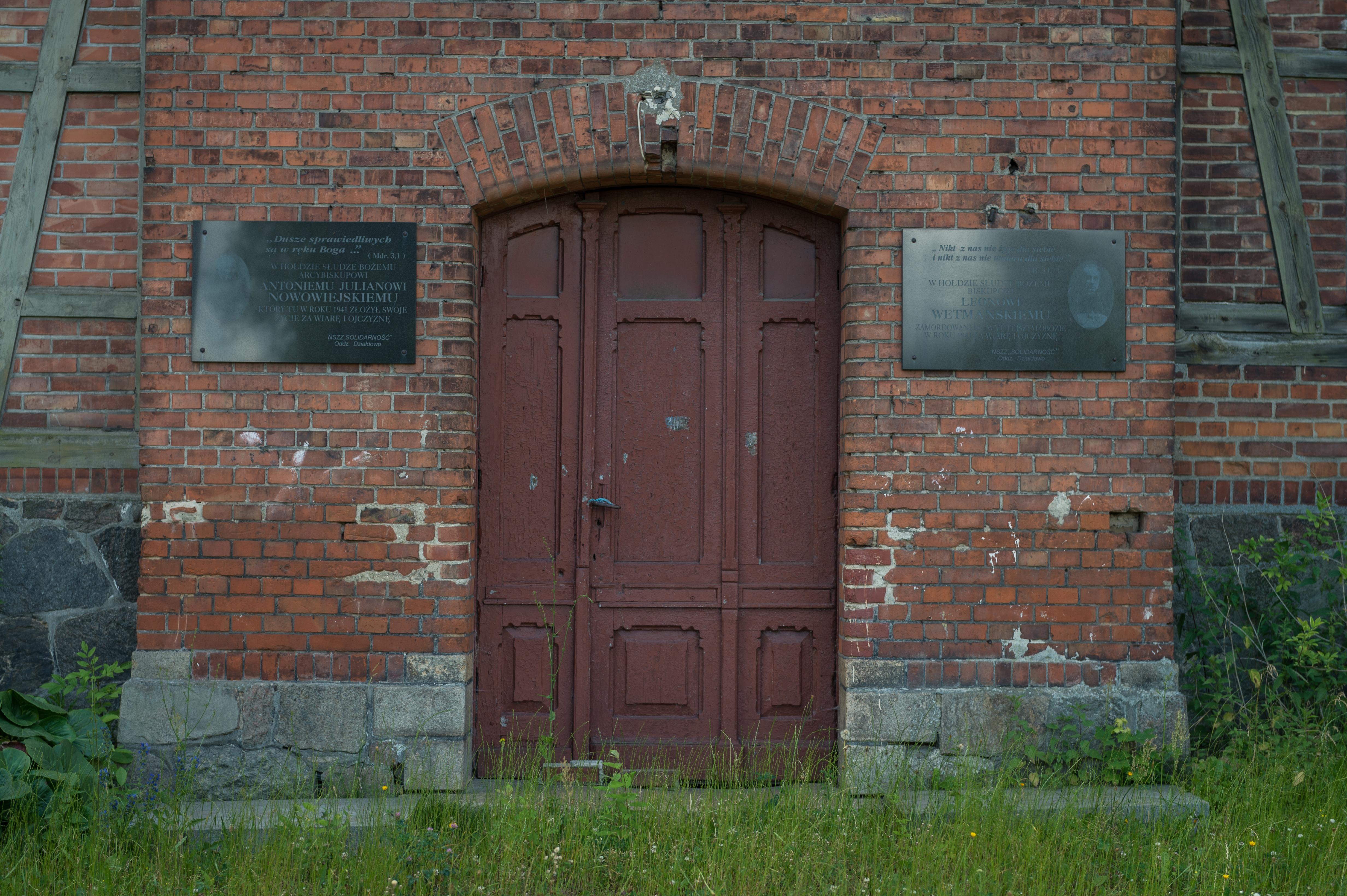 Fotografia przedstawia zrujnowany budynek po KL Soldau wDziałdowie ztablicami upamiętniajacymi biskupów Nowowiejskiego i Wetmańskiego